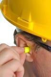 Earplug giallo nell'orecchio Immagine Stock Libera da Diritti