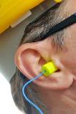 Earplug giallo nell'orecchio Immagine Stock