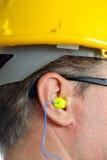 Earplug giallo nell'orecchio Fotografia Stock