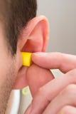 Earplug giallo nell'orecchio immagini stock