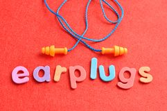 Earplugs with the word earplugs. On a red background Royalty Free Stock Photo