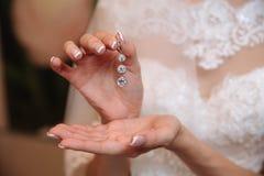 Earrind在新娘的手上 免版税库存图片