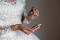Earrind dans les mains de la jeune mariée sur le fond noir Concept des bijoux Photo libre de droits