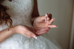 Earrind dans les mains de la jeune mariée sur le fond noir Concept des bijoux Photos stock