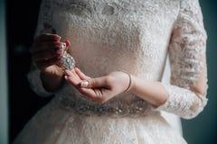 Earrind dans les mains de la jeune mariée sur le fond noir Concept des bijoux Photo stock