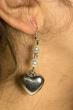 Earring. Handmade earring hanging on the female ear Stock Photography