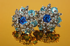 Earring with blue stones. On gold background Stock Images