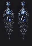 Earring with colorful blue gems on black stock images