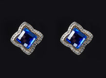 Earring with colorful blue gems on black Royalty Free Stock Photo