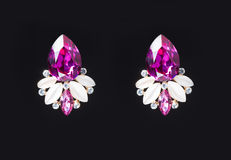 Earring with colorful pink gems on black Stock Photo