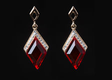 Earring with colorful red gems on black background Stock Images