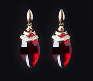 Earring with colorful red gems on black background Stock Photo