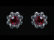 Earring with colorful red gems on black background Stock Photography