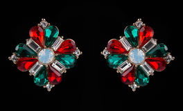 Earring with colorful red and green gems on black Stock Images