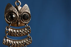 Earring in the form of an owl on a blue background Stock Image