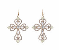Earring the shape of a cross with zircons on white background with zircons on white background Stock Photography
