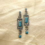 Earrings. With turquoise on a background of white linen and lace Stock Photography