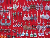 Earrings. Some pairs of earring on red background Royalty Free Stock Photos