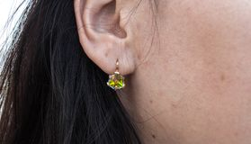 Earrings with the beautiful stone on the ear royalty free stock photography