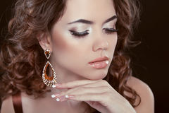 Earrings. Beauty Woman With Long Brown Curly Hair. Hairstyle Stock Photography