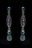 Earrings with blue stones on the black Royalty Free Stock Photography