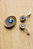 Earrings and brooch. A pair of blue earrings in the shape of heart, earrings on a background of oak, earrings and brooch Royalty Free Stock Photos