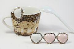 Earrings in the form of hearts. Multi-colored earrings in the form of hearts. On a back background a coffee cup royalty free illustration