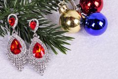 Earrings with red stones on a branch of a Christmas tree with a Stock Photo