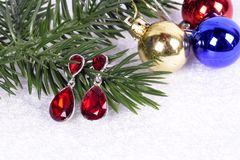 Earrings with red stones on a branch of a Christmas tree with a. Ball Royalty Free Stock Photo