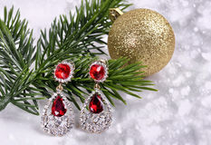 Earrings with red stones on a branch of a Christmas tree with a ball on an abstract background. Earrings with red stones on a branch of a  Christmas tree with a Stock Image
