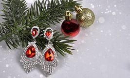 Earrings with red stones on a branch of a Christmas tree with a ball on an abstract background Stock Images