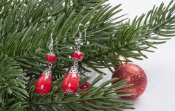 Earrings with red stones on a branch of a Christmas tree with a ball Stock Image