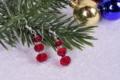 Earrings with red stones on a branch of a Christmas tree with a Stock Images