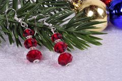 Earrings with red stones on a branch of a Christmas tree with a Royalty Free Stock Image