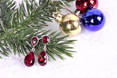 Earrings with red stones on a branch of a Christmas tree with a Royalty Free Stock Photo