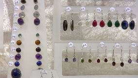 Earrings for sale. Various shape and colour color earrings and studs on retail sale display with British pound price tags stock video footage
