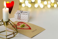 Earrings in the shape of hearts on a card says Forever. Candle in diamond shaped candlestick Stock Photo