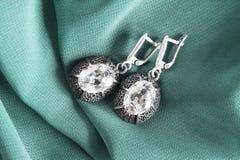 Earrings on silk Stock Images