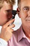 Ears del doctor Examining Male Patient's Imagen de archivo libre de regalías