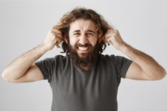 Ears are tired from hearing lies. Studio shot of bothered and depressed mature guy with beard and curly hair pulling. Ears and grimacing from pain, being Stock Photography