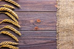 ears of wheat and cloth on wooden background royalty free stock images