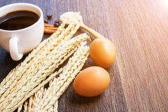 Ears of wheat and coffee with egg on a dark wooden table background. royalty free stock images
