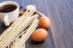 Ears of wheat and coffee with egg on a dark wooden table background. royalty free stock photos
