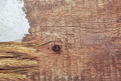 Ears of wheat and flour on wooden background Royalty Free Stock Image