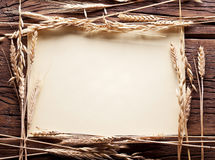 Ears of wheat in the form frame. Ears of wheat in the form frame on old wooden table Stock Photos