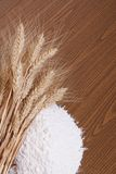 Ears of wheat and a heap white flour on a wooden table Stock Photos
