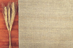 Ears of wheat and linen cloth on wooden background top view Royalty Free Stock Photo