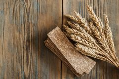 Sheaf of wheat as bread gifts of warm summer. Ears of wheat on old wooden table Royalty Free Stock Photo