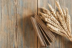 Sheaf of wheat as bread gifts of warm summer. Ears of wheat on old wooden table Stock Photo