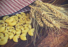 Ears of wheat and pasta. Vintage toned picture of the ears of wheat with pasta on the wooden background Royalty Free Stock Image